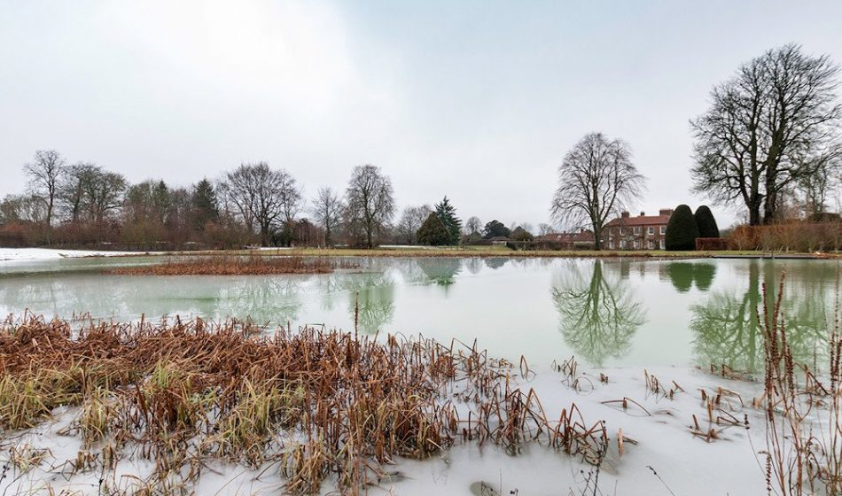 Manor House Hampshire - a Lake in Winter with a house and trees in the background